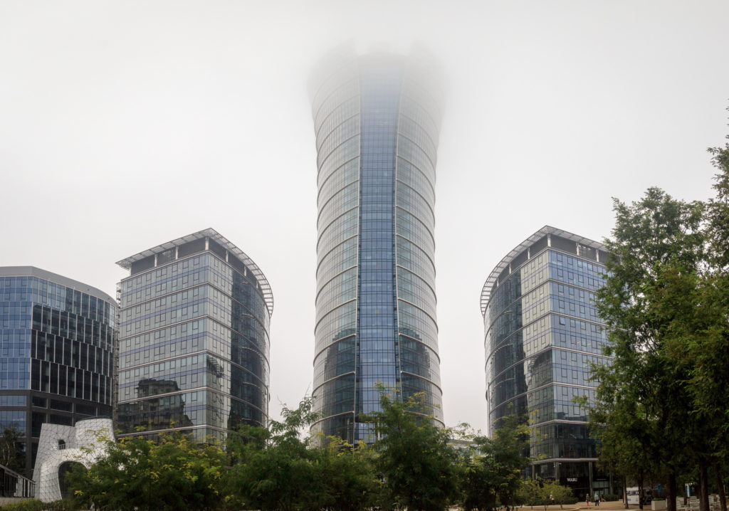 The photo shows four glass buildings with silver and grayish blue tones. The leftmost building, cut-off at the edge of the photo, is the lowest, with a plain surface and irregular shape. To its right is a slightly taller semi-cylindrical building, with a flat side facing diagonally towards the left of the photo. At the center is a tall building that reaches the photo's upper edge, with a cylindrical shape that opens up slightly at the top. This building has a vertical strip of blue glass, while silver glass covers the rest of its exterior. Finally, to the right is a building identical to the previously mentioned semi-cylindrical one, but with its flat side facing towards the right. In front of the buildings are some small trees with dark green leaves. The sky in the back is cloudy.