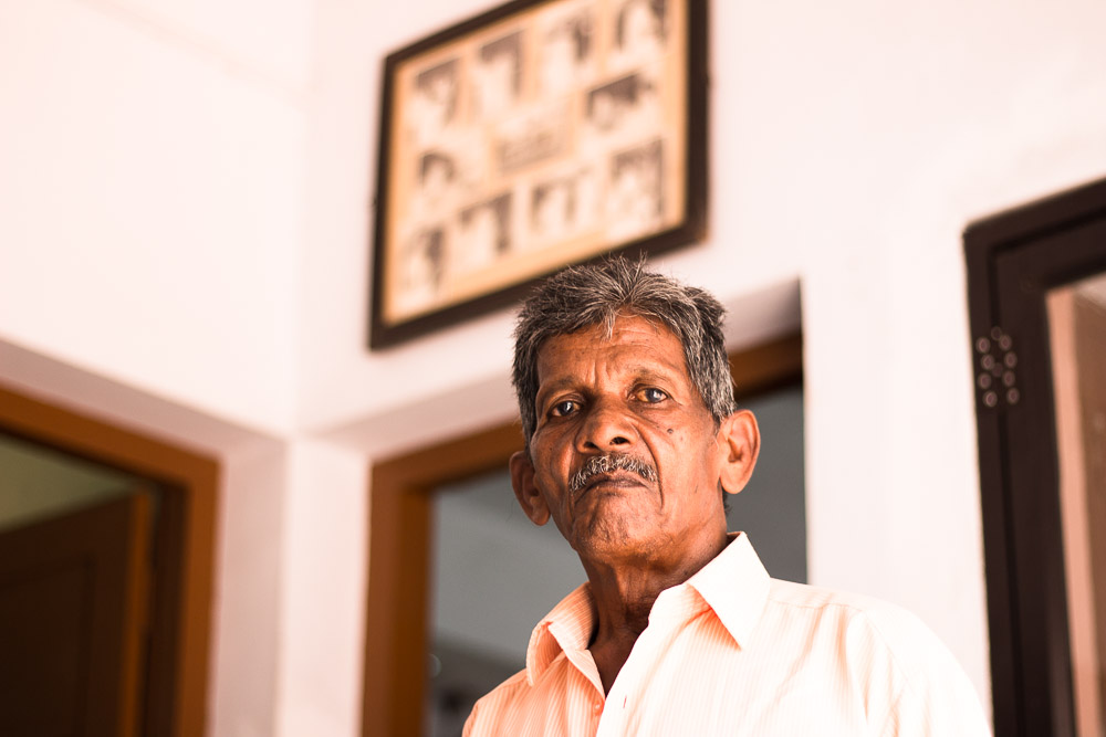 The photograph shows the bust of an older man with short, graying hair, bronze skin, close to 80 years old, looking at the camera with a serious expression and lightly pursed lips. He has a graying moustache and wears a very light pink button-up shirt. In the background is the corner between two white walls: on the left wall is an open door that goes to the edge of the photo, while the right wall has two open doors that also go to the edge of the photo. Above the middle door is a sepia-toned picture with a dark brown frame. The walls and its doors, as well as the picture on the wall, are out of focus. The place is well lit and the light is hitting the man's left side.