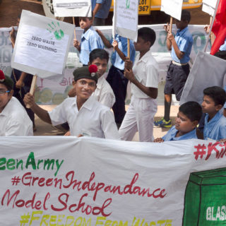 """Young Indian boys march together, holding a white banner written """"#GreenArmy #Indepandance #ModelSchool,"""" along with other signs cut-off at the edges of the photo, and with drawings of recycling receptacles. Some are wearing white shirts and dark green berets with a red tuft, while others are wearing light blue shirts and dark blue shorts. Three of the boys wearing white shirts are smiling to the camera, and one of them is also holding a poster with the words """"zero waste, zero warming."""" The boys in the background are looking straight ahead, some of them holding posters with writing that is out of focus. The camera is to the right of the march."""