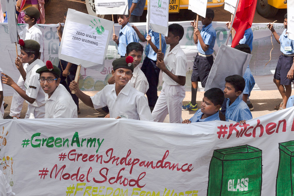 "Young Indian boys march together, holding a white banner written ""#GreenArmy #Indepandance #ModelSchool,"" along with other signs cut-off at the edges of the photo, and with drawings of recycling receptacles. Some are wearing white shirts and dark green berets with a red tuft, while others are wearing light blue shirts and dark blue shorts. Three of the boys wearing white shirts are smiling to the camera, and one of them is also holding a poster with the words ""zero waste, zero warming."" The boys in the background are looking straight ahead, some of them holding posters with writing that is out of focus. The camera is to the right of the march."