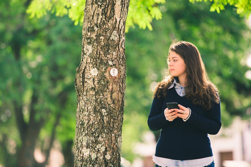 O mesmo tronco de árvore da foto anterior, com a pequena placa circular contendo um QR code, aparece mais distante, ao centro da foto. À direita, uma jovem de pele branca e cabelos lisos, longos e castanhos segura um celular preto e olha para a placa. A jovem veste uma camisa azul clara por baixo de um suéter azul marinho. Ao fundo, folhagens desfocadas.