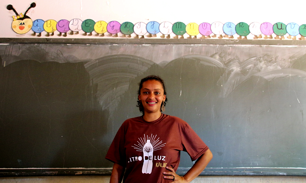 """A woman smiles at the camera, her left hand resting on her hip. She has black skin and dark curly hair tied into a ponytail. She is wearing brown earrings shaped like water drops and a dark brown t-shirt with the """"Litro de Luz"""" logo printed in white on the chest. Behind her is a green chalkboard, above which is glued a colorful paper caterpillar with the letters of the alphabet printed on each section of its body. The wall is white."""