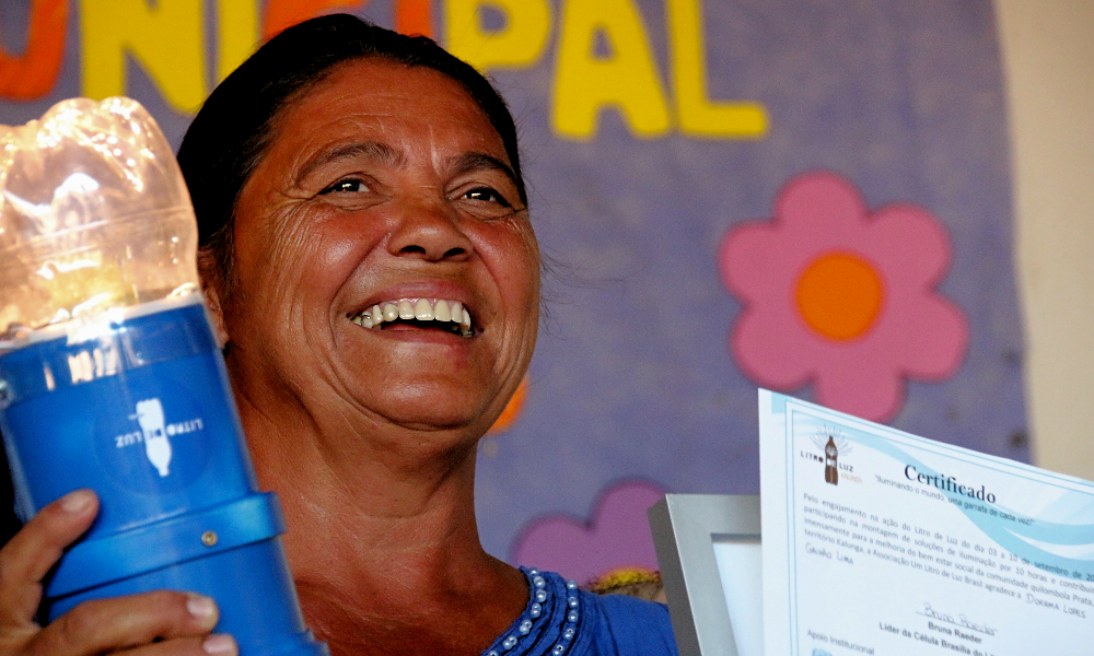 """A woman smiles, facing diagonally towards the right side of the photo. She is holding a plastic bottle lamp in her right hand, and a certificate printed on white paper in her left hand, with the word """"certificate"""" written on it in Portuguese in dark blue and the """"Litro de Luz"""" logo printed in brown. The woman has reddish skin and straight black hair, tied back. In the back is part of a large purple poster with yellow letters."""