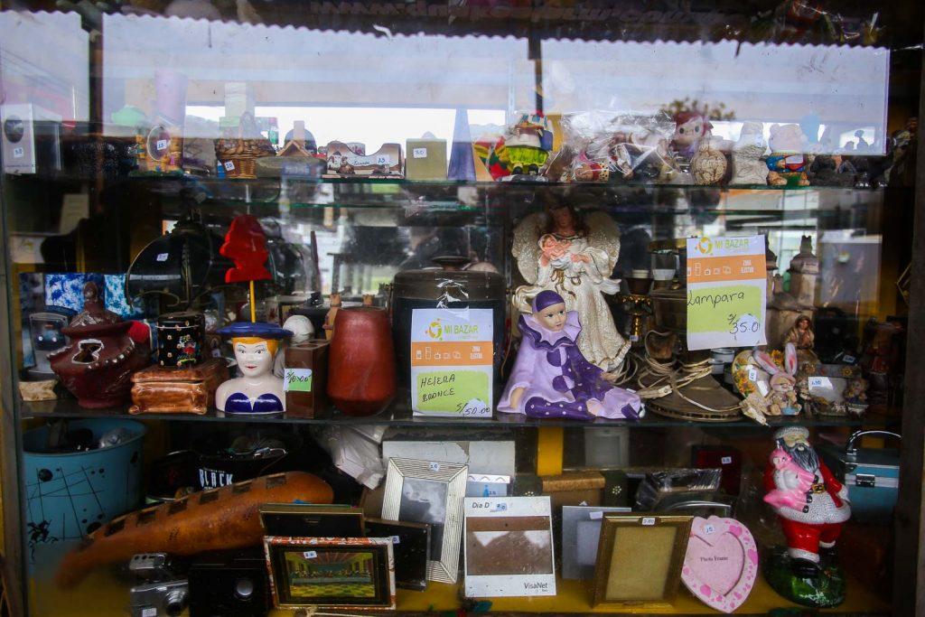 Un escaparate con tres baldas de cristal repletas de objetos diversos, decorativos: marcos de fotos, cajitas y baúles, muñecas, lámparas…