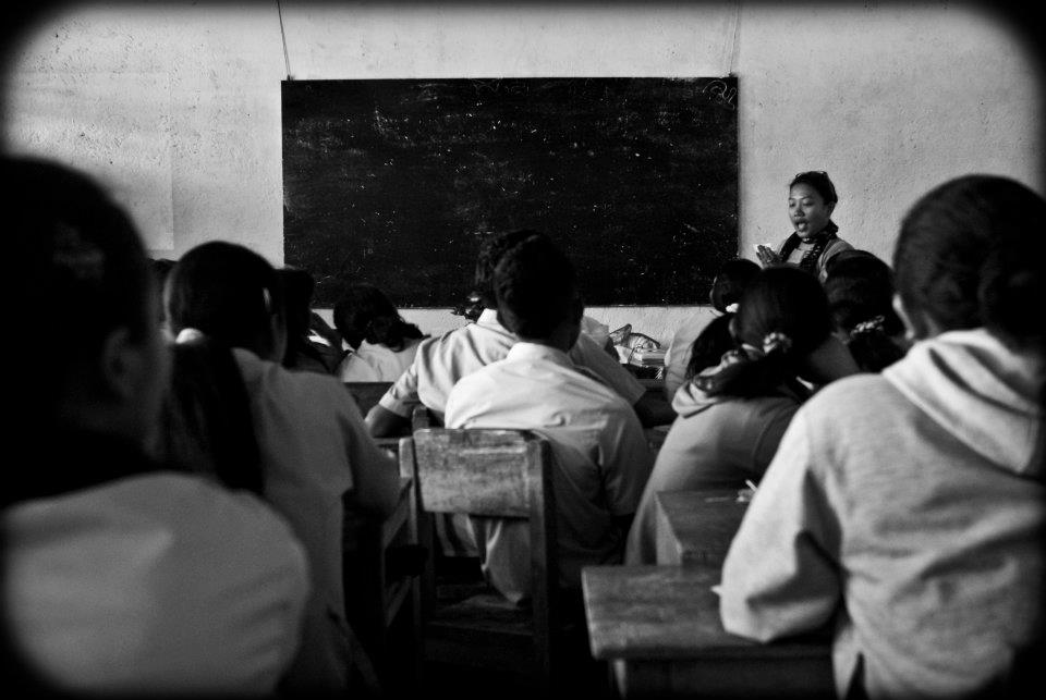 A black and white photo shows children sitting in rows on wooden chairs, their backs to the camera. In front of the children appears a standing woman's face, with a talking expression. The woman has dark skin and dark hair, tied back. In the background is a white wall with a large blackboard hanging on it.