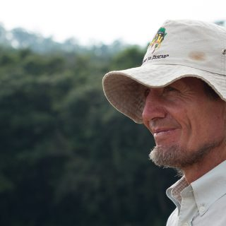Profile picture, a bearded man in his fifties wearing a hat looks at the horizon. There are many unfocused trees in the background.