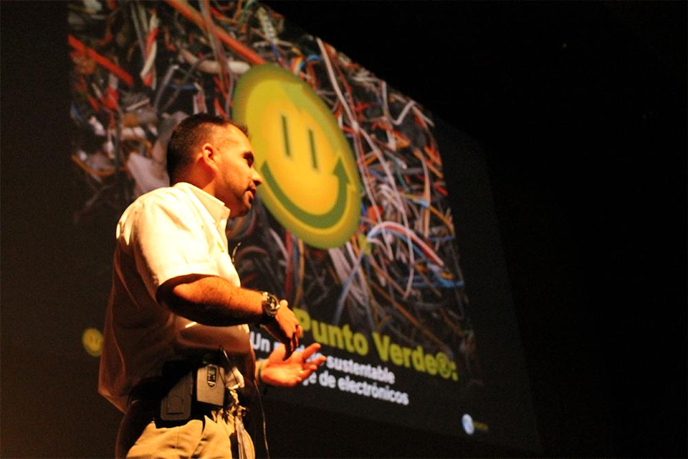 """Foto de Alvaro em um palco, fazendo uma palestra. Ao fundo, um telão mostrando um emoji feliz e escrito """"Punto Verde"""". Na foto, vemos Alvaro, vestindo uma camisa branca, de perfil, da cintura para cima"""