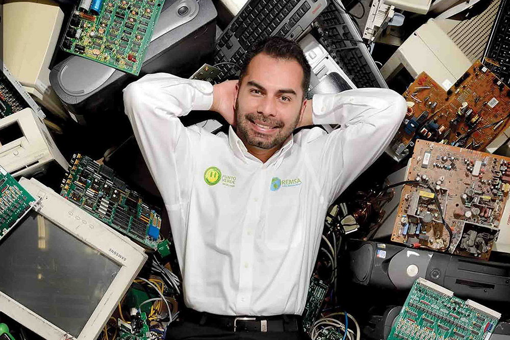 Photo of a white man with beard and mustache, wearing a white shirt and smiling at the camera. He is lying on top of a lot of screens and computers. In the photo, it appears from the sintura upwards