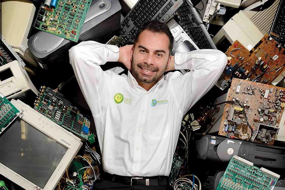Homem branco, com barba e bigode, vestindo uma camisa branca e sorrindo para a câmera. deitado em cima de telas e monitores de computador. A imagem mostra apenas seu corpo da cintura para cima.