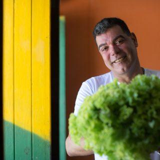 En la foto, un hombre blanco, pelo gris, sonríe a la cámara mientras sostiene un gran pie de lechuga verde