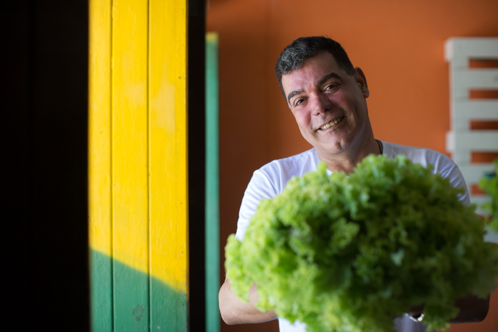In the photo, a white man, gray hair, smiles at the camera while holding a large green lettuce
