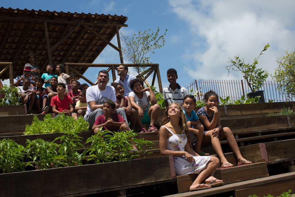 The picture shows Demetrius with a group of young people and children, sitting on the rooftop of the ecoproductive and green roof. Beside, a flowerbed with several greens. Everyone is smiling and looking at the camera.