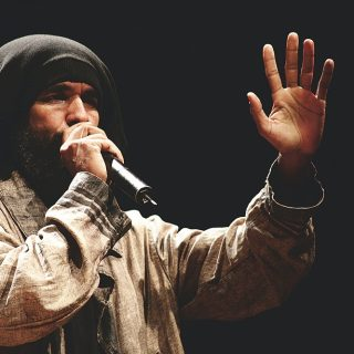 A man with brown skin, brown curly beard and a black cloth covering his hair talks into a microphone. He is wearing a loose light brown shirt made of light cotton, and is facing diagonally towards the right side of the photo, his left hand held up and open, showing his palm. His right hand holds the microphone up to his mouth. The background is black.
