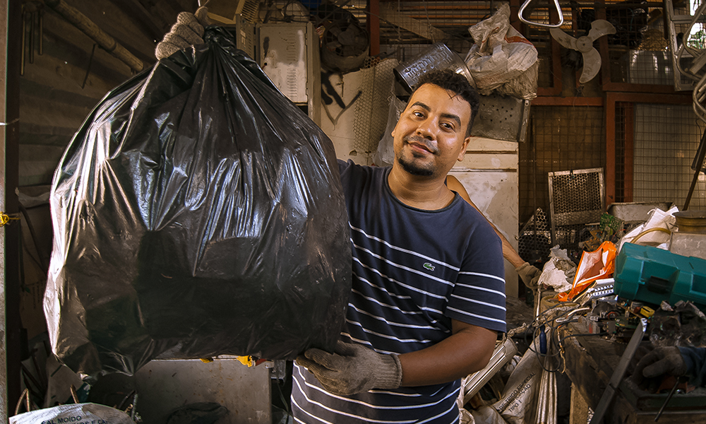 Picture of a man holding a big black trash bag, looking at the camera and smiling