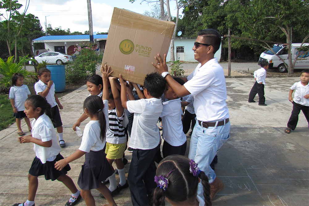 A man, medium height, carrying a large cardboard box. With him, a group of several children under 10 years old, helping to carry the box