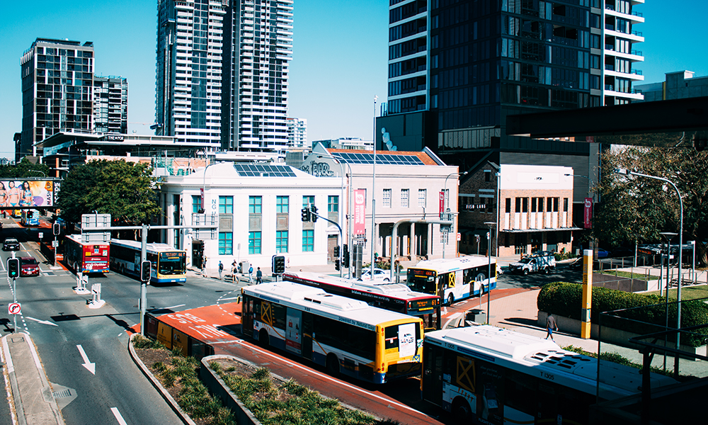 The picture shows Brisbane downtown. There's a crossroads with several buses and buildings. Two of the buildings, of two floors each, hold photovoltaic boards at the roof.