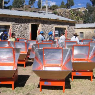 The picture shows more than ten solar cookers in an open space. In the background, a group of houses made of stone. Amidst these cookers (which look like wooden and aluminum boxes) are ten people, most of them with their back turned toward the camera, wearing protective helmets.