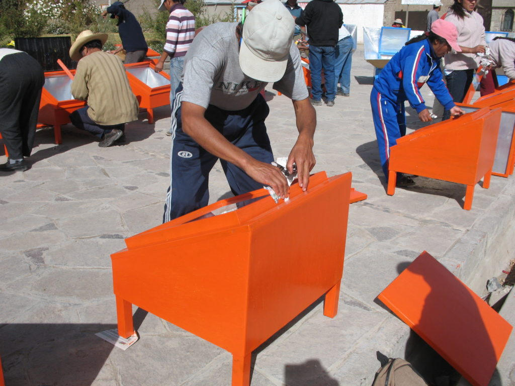 The picture shows a group of more than ten people. They are putting the final touches on solar cookers they have made. In the foreground is a man of medium height, wearing a cap, with his head down (we cannot see his face). He is varnishing the solar cooker (a wooden box with a glass lid, approximately one square meter in size).