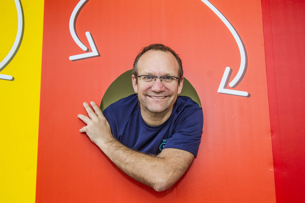 A balding man, about 50 years old, smiling broadly, wearing glasses and a blue t-shirt, emerges from an orange recycling box. On the box, two arrows point towards the man.