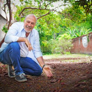 """Um homem de barba, careca, e com alguns fios de cabelo grisalhos, aparentando ter por volta dos 50 anos, veste tênis, calça jeans e uma camisa branca. Ele está agachado, sorrindo para câmera, em uma espécie de """"beco"""", com folhas secas no chão e árvores ao redor"""