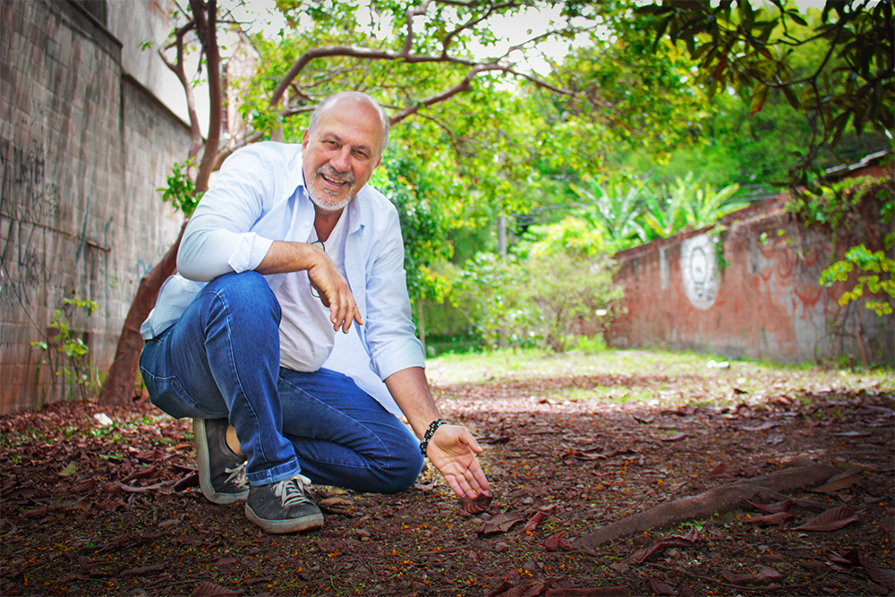 A bearded, bald with a few gray hair man, around the age of 50, wearing sneakers, jeans and a white shirt. He is crouching and smiling at the camera. He is in an alley with dry leaves on the ground. There are trees in the background.