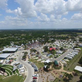 La foto muestra una imagen aérea de un espacio donde se ven varios motorhomes y pequeñas casas, rodeado de una área verde.