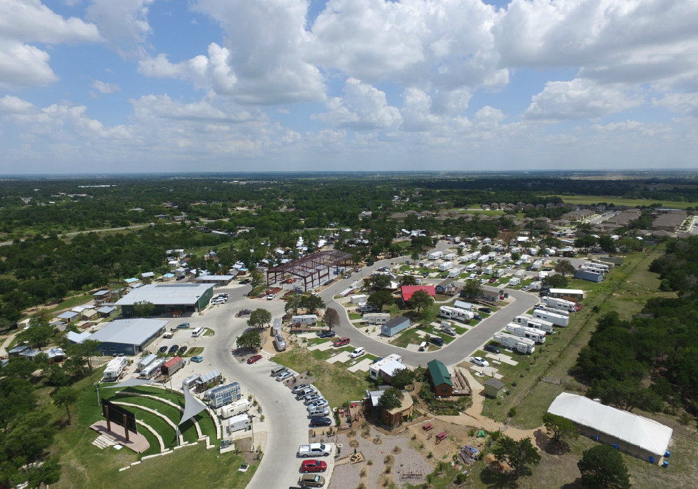An aerial image showing several motorhomes and small houses surrounded by green trees.