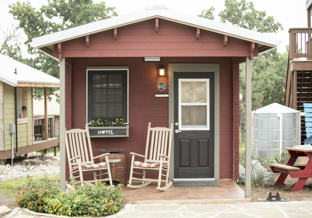 "A small, brown, wooden house with a window and a door and two rocking chairs in front of it. There is a small windowbox, with flowers growing in it, bearing the word ""Home"" on the front. The ""O"" in ""home"" is a heart shape."