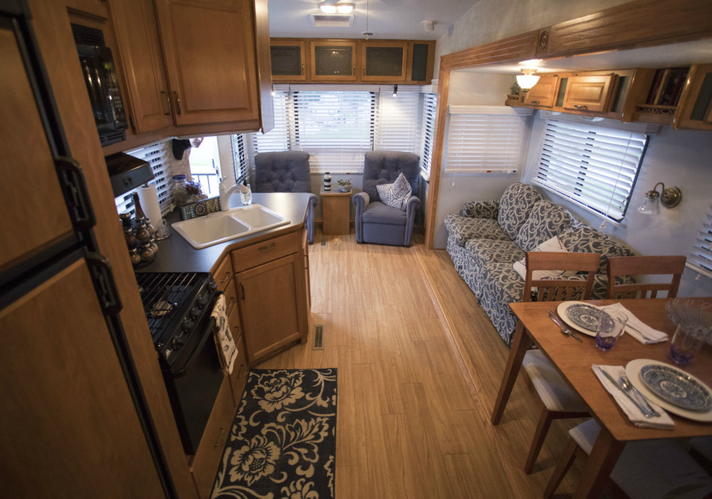The picture shows the interior of a motorhome with floor and furniture all finished in wood. On the left side is the kitchen, with a small stove, a sink and some cabinets. A living room, with sofas and armchairs, can seat five people. On the right side is a dining table with some chairs, set with some plates in an intricate blue and white pattern.