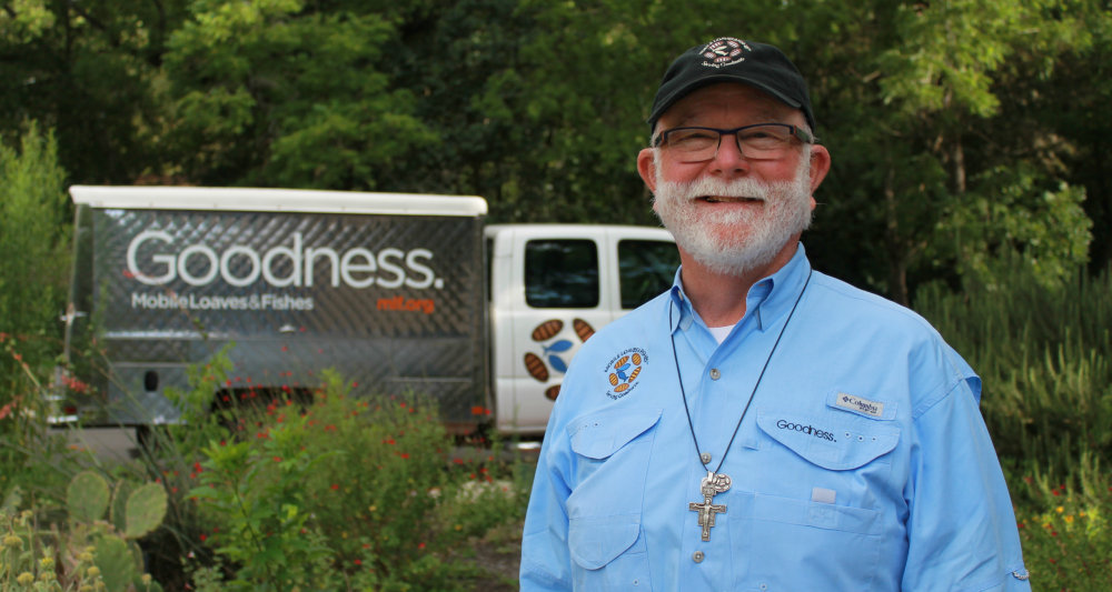 "A white man with a white beard, wearing a blue shirt, glasses and black cap. He is smiling at the camera. There is a truck behind him with the word ""Goodness"" inscribed upon it."