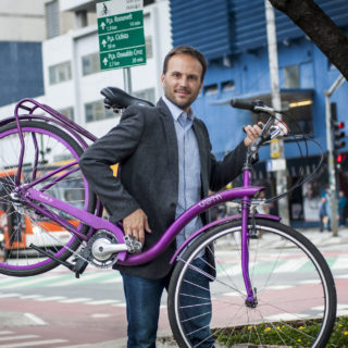 A brown-haired, lightly-bearded, white man wearing jeans, a light blue shirt and a dark gray blazer holds a purple bike. In the background is an intersection with bike paths, pedestrian lanes and a municipal bus.