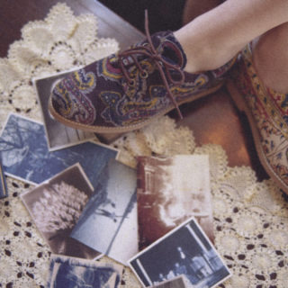 The ankles and feet of a thin, white woman are shown in the upper right corner of the image. She is wearing embroidered fabric shoes and her feet are crossed. At her feet are several blue and brown color photos, a book with a blue cover, a notebook with a brown cover (in the left corner) and part of a cream-colored, embroidered rug on the wood floor.