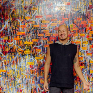 A bald, Japanese man with a small beard. He wears a blue shirt and dark gray pants. He is looking to his right side and smiling. There is a wall painted colorfully with graphite in the background.