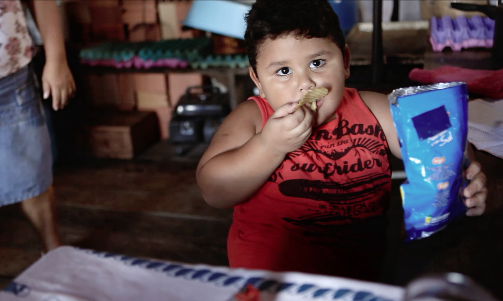 A chubby boy with short black hair, brown eyes and dark skin is eating some potato chips, his hand to his mouth. He looks at the camera, holding up the blue packaging of the snack.