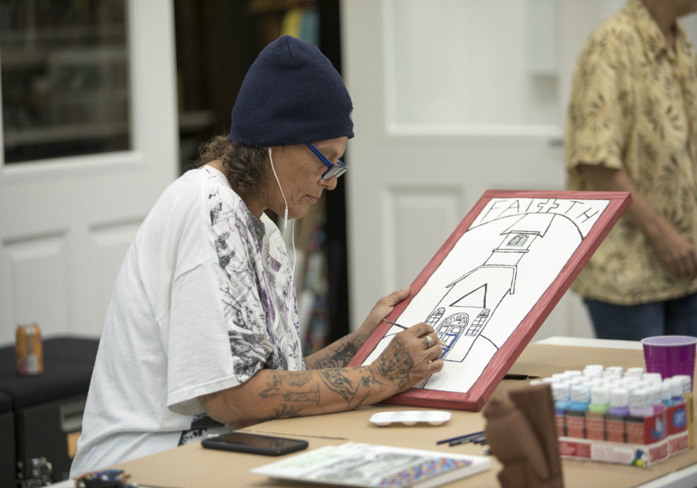 "A white woman with tattoos on her arms. She is wearing a white T-shirt, glasses and a blue winter hat. She is drawing a church and writing the word ""Faith"". She is in an atelier, and in front of her are paints and brushes."