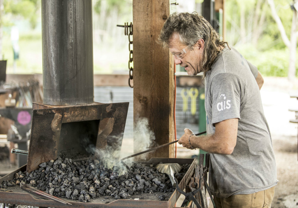 The picture shows a man with light gray hair holding an iron poker in his hand and tending hot coals. In the background, out of focus, is a workshop full of tools. He is, at least partly, in an open-air structure, with trees around.