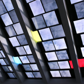 A close-up of glass cut into squares, with clouds and blue sky reflected in most of them. Three stand out, reflecting something else: the colors red, yellow and green. Each group of 15 glass squares is separated by a steel beam.