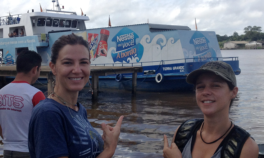 A thin white woman with her brown hair up is in the left side of the picture, smiling at the camera. Standing next to her, another thin white woman, shorter than her companion, is wearing a black cap and a backpack. She also smiles at the camera. Both are pointing at a boat in back of them, docked in muddy waters, decorated with the Nestlé logo and pictures of Nestlé products.