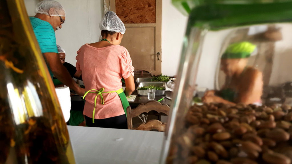 As if the camera is on the back wall of a shelf, a glass bottle is to the left, and part of a glass jar of beans is on the right. Both objects are blurry. In the kitchen, a woman and man, both wearing white caps on their heads, have their backs to the camera. They are cutting vegetables. Next to them, through the jar of beans, another woman, her image blurred by the glass, wears a green cap. She seems to be peeling some vegetables.