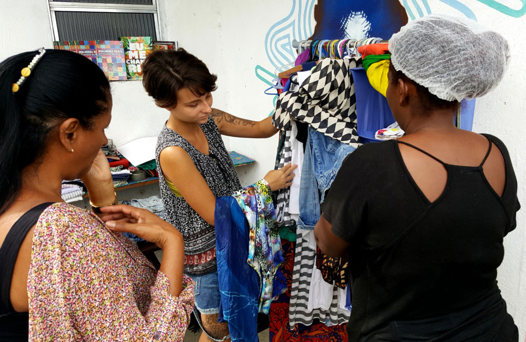 A thin, white woman with short black hair is showing a rack of clothing to two other women whose backs face the camera.
