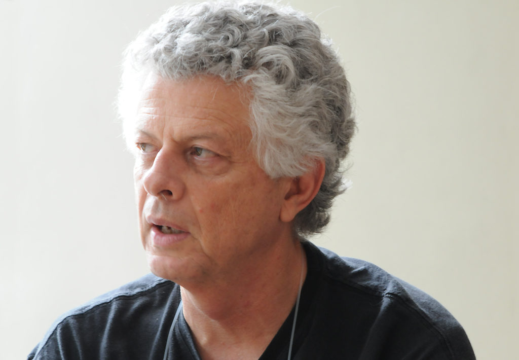 Photograph of a man with gray hair wearing a black shirt.