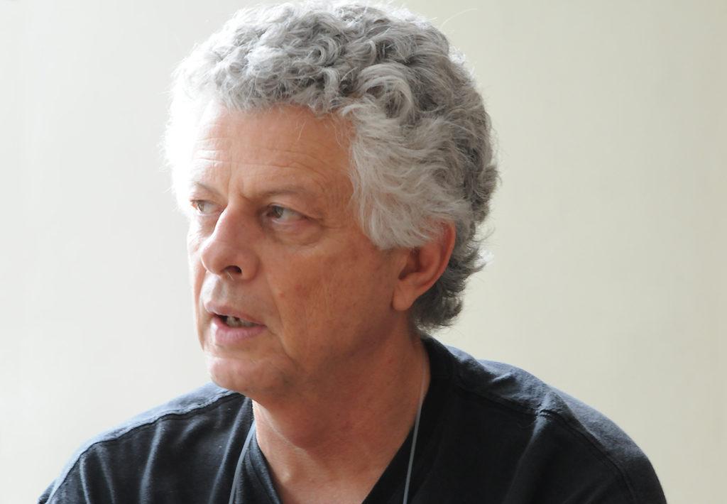 Foto de um homem de cabelos brancos com blusa preta.