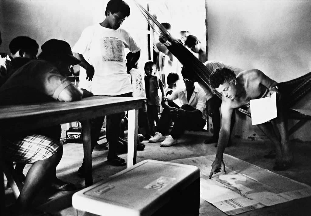 A black and white photograph of a room full of people. One man is sitting in a hammock and pointing to a map on the floor in front of him. Two other men sit at a table, one man stands next to the hammock, and another sits on the floor in the doorway with children standing around him.