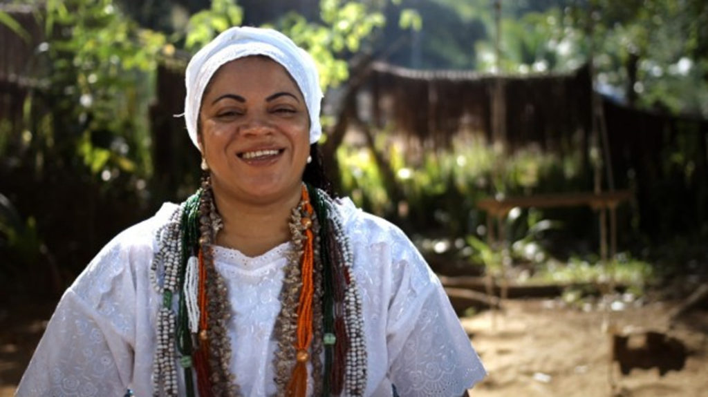 A black woman wearing a white turban, a white blouse and several colored beaded necklaces smiles at the camera. She is standing in a yard with lots of plants.