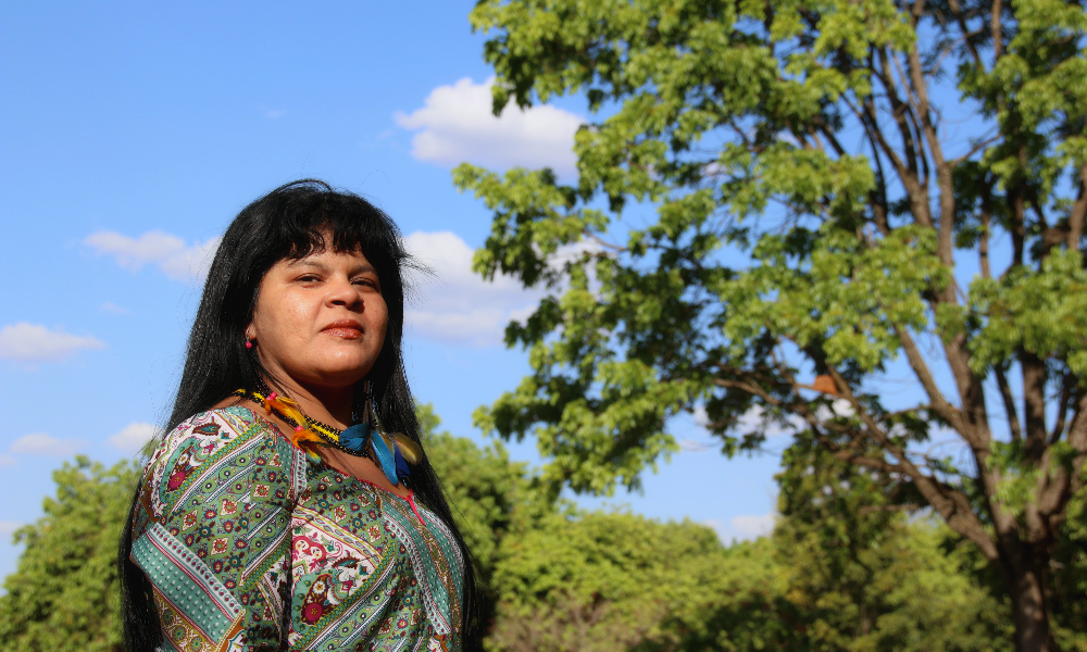 A middle-aged indigenous woman with long black hair and bangs, wearing a printed blouse. There are trees in the background.
