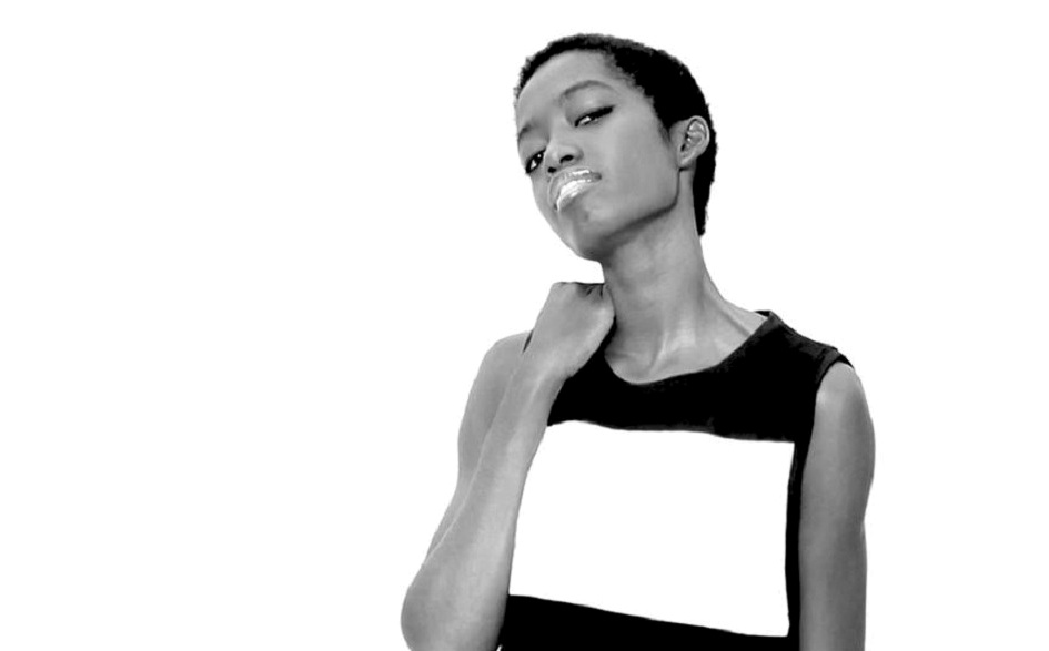 A thin black woman with very short hair, on the right side of the black and white photo, is looking at the camera. She wears a black shirt with a large, horizontal, white stripe. Her chin is slightly tilted up, and her right hand rests on top of her right shoulder. Her body is shown only from the waist up.