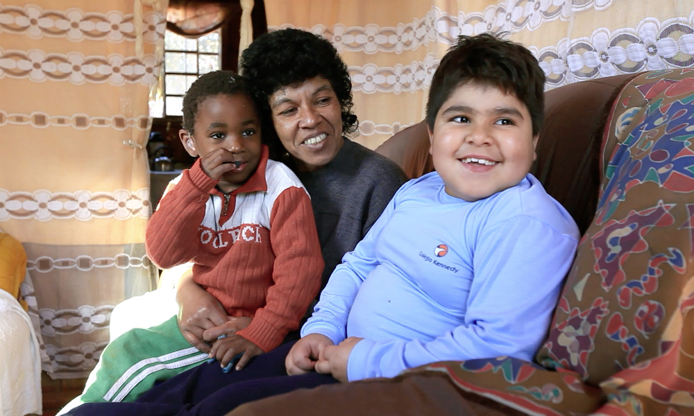 A black, curly-haired woman is sitting with a little boy, also black and slim, on her lap on a brown couch. Next to them on the couch is another boy, who is very chubby, with lighter skin, brown hair and brown eyes. Both the mother and the bigger boy are smiling,. She is looking at him, and he is looking at someone who seems to be behind the camera.