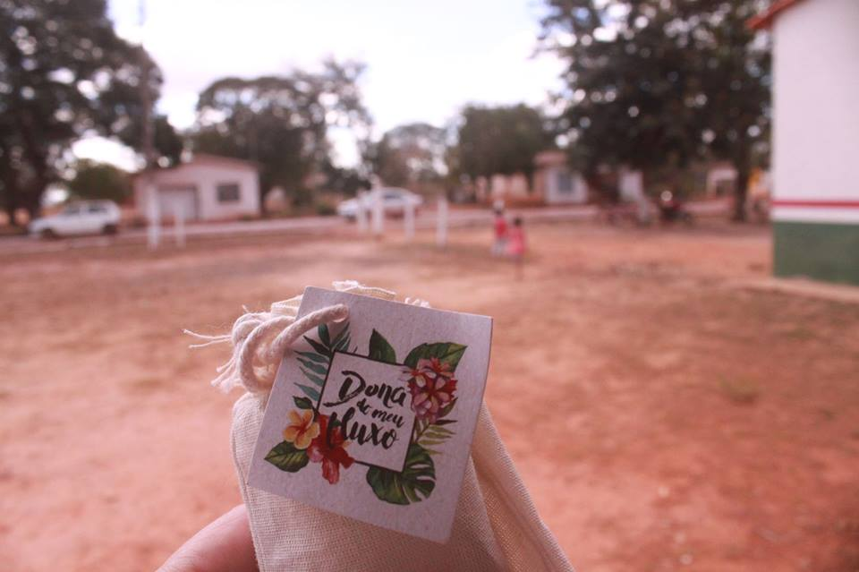 "In the foreground, part of a white hand holds a small beige fabric bag, tied with a string. On the bag there is a small, square, paper card decorated with an image of flowers and the inscription: ""Owner of my Menstrual Flow."" In the background is sandy soil, some small houses and a couple cars, out of focus."