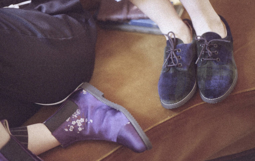 We can see the ankles and feet of two white people on a brown background. One of them is wearing purplish-blue shoes with shoelaces. The other wears lilac boots which only cover part of the ankle and are decorated with small, white flowers.