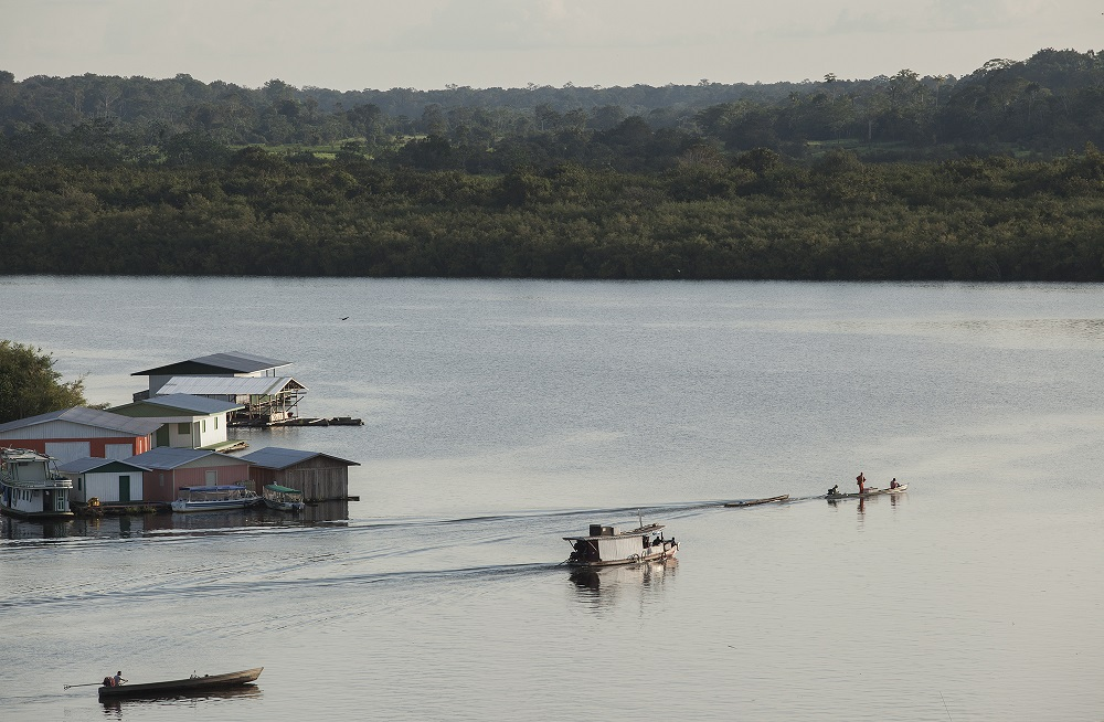 La imagen muestra un gran río de color azul oscuro, donde dos pequeñas embarcaciones de vela y un conjunto de 6 casas parecen suspendidos sobre palafitos a orillas del río. El río está rodeado de vegetación y árboles.
